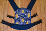 Load image into Gallery viewer, Olives and Applesauce BeezNeez doll carrier has a royal blue background with yellow bee hives on blue tables, with white ferns and white and blue flowers. Small yellow bees are flying all over. It has matching navy blue shoulder straps and waistband.