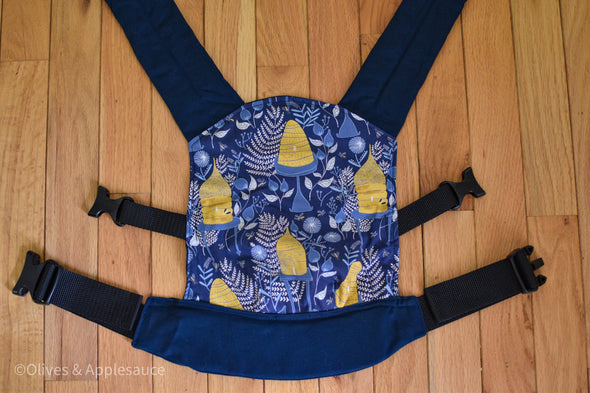 Olives and Applesauce BeezNeez doll carrier has a royal blue background with yellow bee hives on blue tables, with white ferns and white and blue flowers. Small yellow bees are flying all over. It has matching navy blue shoulder straps and waistband.