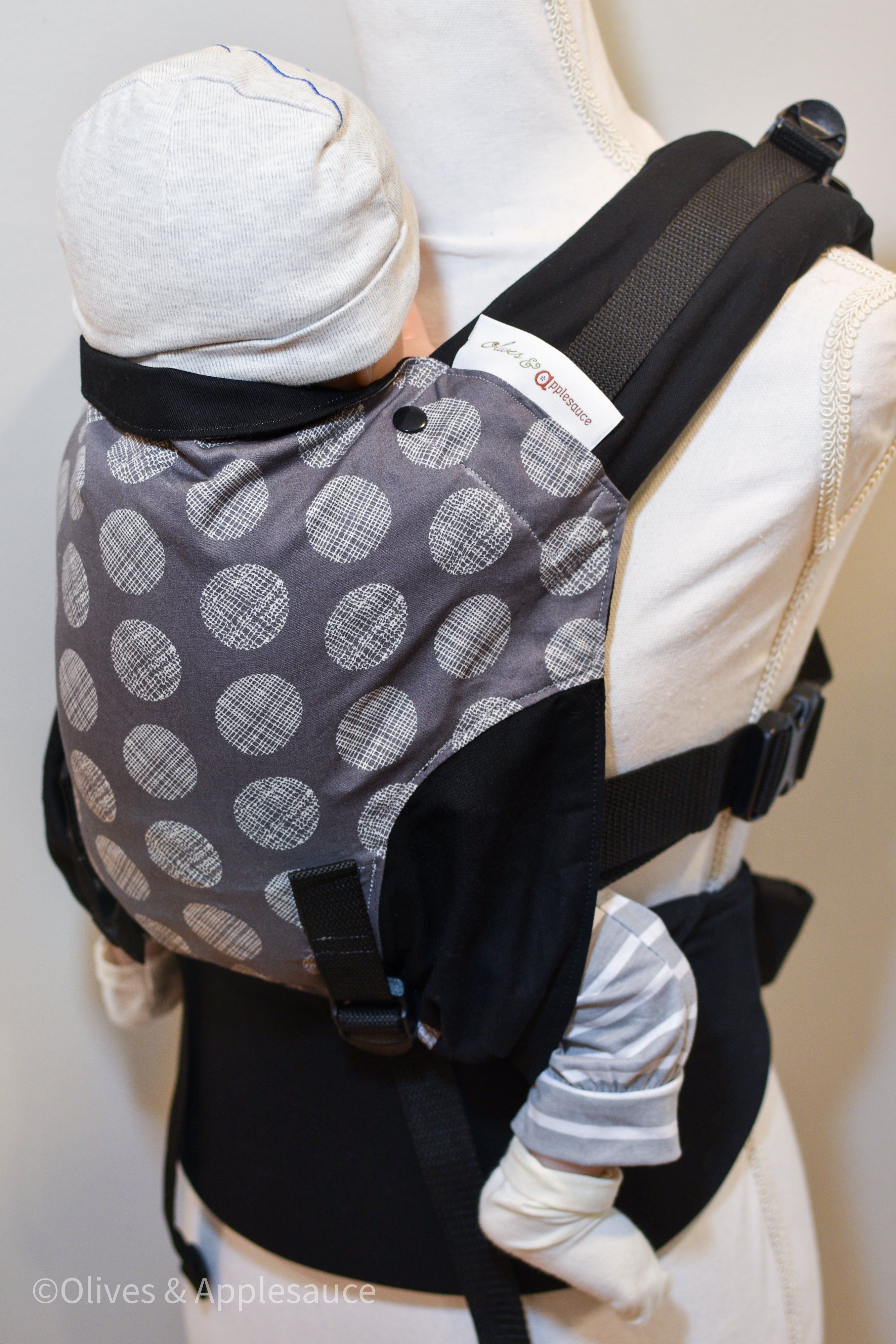 Olives and Applesauce Cross Hatch Olympia carrier on a dress form sized for a newborn. Hatch is a dark grey panel with white circles that have patterns of lines inside the circles. It is paired with black twill. Due to Olympia's unique design, the print is in an hour glass shape with twill sewn in to complete the body panel.
