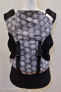 Olives and Applesauce Cross Hatch Olympia carrier on a dress form sized for a preschooler. Hatch is a dark grey panel with white circles that have patterns of lines inside the circles. It is paired with black twill. Due to Olympia's unique design, the print is in an hour glass shape with twill sewn in to complete the body panel.