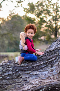 A little girl wearing an Olives and Applesauce Cross Hatch Doll carrier on her back with her stuffed bunny rabbit while she climbs a tree smiling