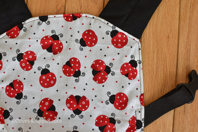 Close up of the Olives and Applesauce LuckyBug Doll Carrier. It is a white panel with red, white, and black ladybugs all over it. It has black Shoulder straps and waistband.