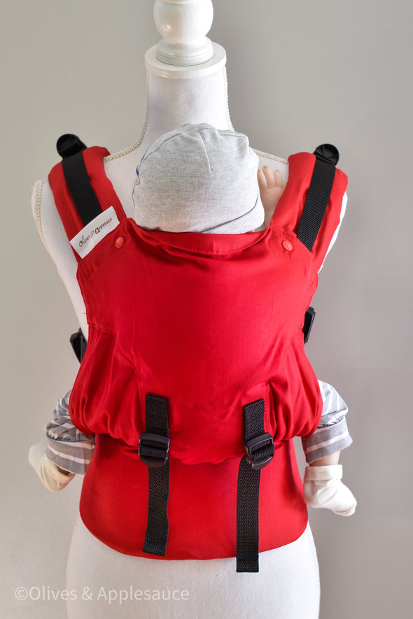 Solid red Olives and Applesauce Olympia Carrier on a dress form. Due to Olympia's unique design, the red twill is in an hour glass shape with more twill sewn in to complete the body panel, with height adjusters sewn on the front. In this image the carrier is adjusted to fit a small babies