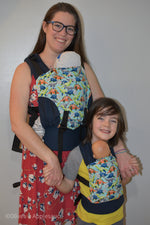 Load image into Gallery viewer, Olives and Applesauce Roam Olympia carrier worn by a mother with a newborn and Olives and Applesauce Roam Doll Carrier worn by a 6.5 year old