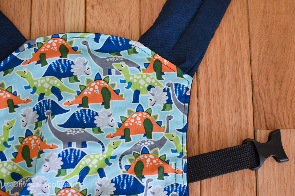 Olives and Applesauce roam doll carrier. Roam has green, dark blue, and orange glow in the dark dinosaurs on a light blue panel with navy blue twill.