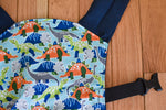 Load image into Gallery viewer, Olives and Applesauce roam doll carrier. Roam has green, dark blue, and orange glow in the dark dinosaurs on a light blue panel with navy blue twill.