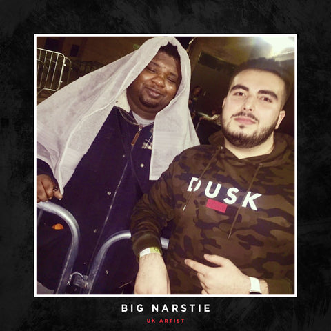 Big Narstie posing with a DUSK Empire Camo jumper.