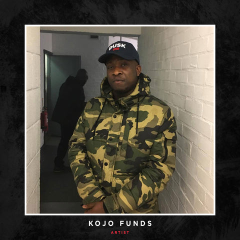Kojo Funds posing with a DUSK Empire cap.