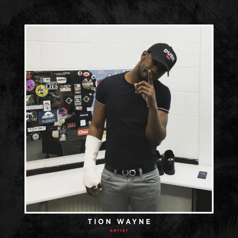 Tion Wayne posing with a DUSK Empire cap.