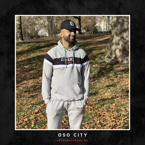 OSO City posing with a DUSK Empire tracksuit.