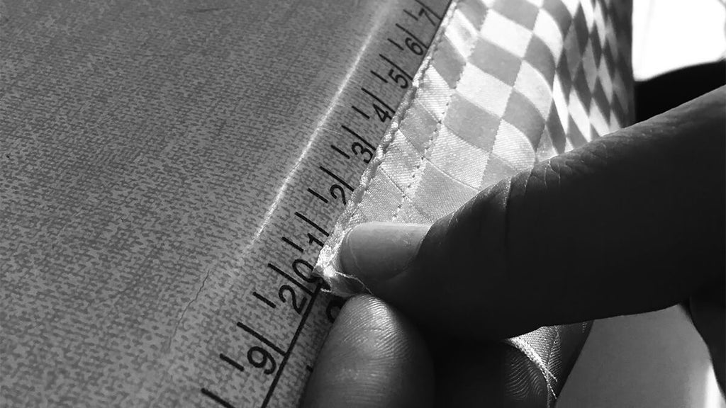 Clairevoire tailor carefully measuring length of craft