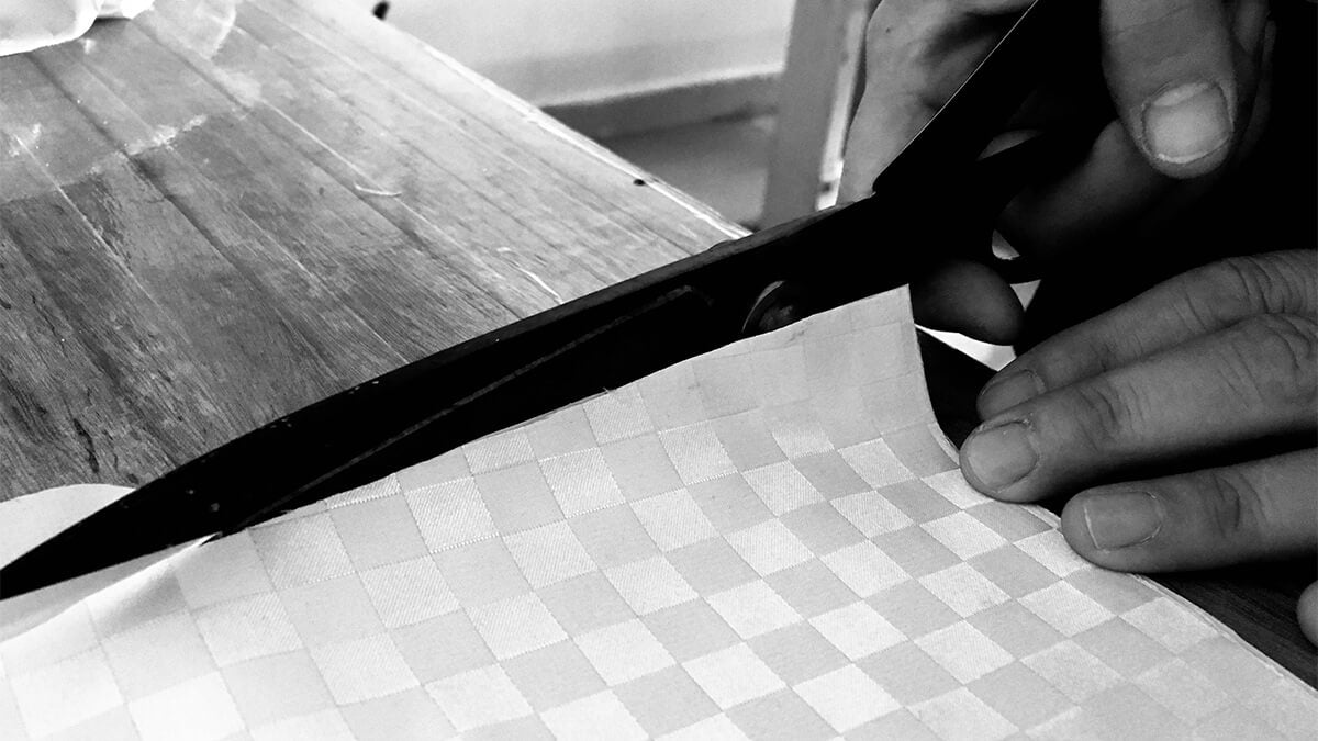 designer cutting a piano cloth fabric