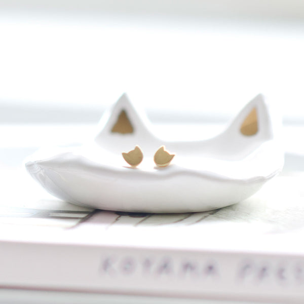 gold stuf cat earrings in dish
