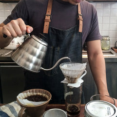 Barista pouring hot water over coffee in a filter for pour-over coffee.