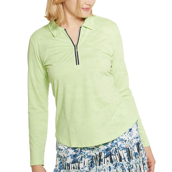 A woman modeling an apple-colored long-sleeved top with a floral fringe skirt