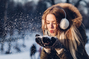 a girl wearing earmuffs blowing snow out of her mittens