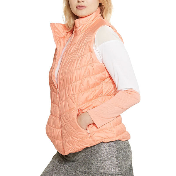 A woman modeling a melon-colored vest over a long-sleeved top and a grey skirt