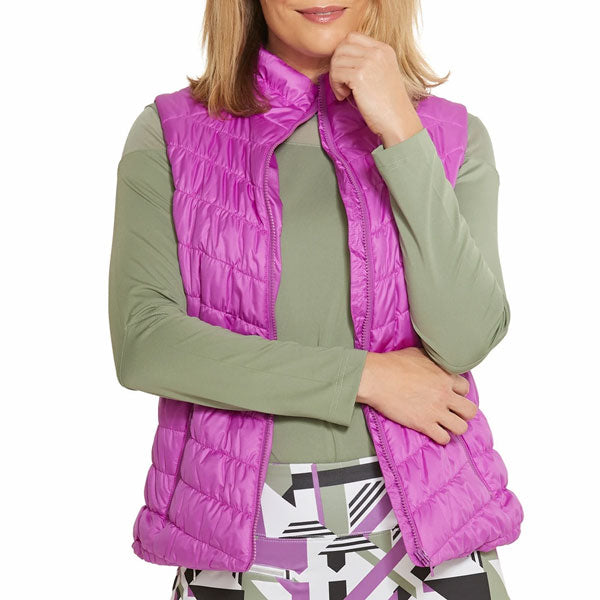 A woman modeling an orchid-colored vest over an olive top