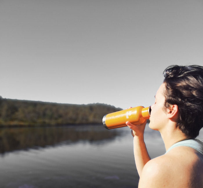 woman drinking bottle at lake