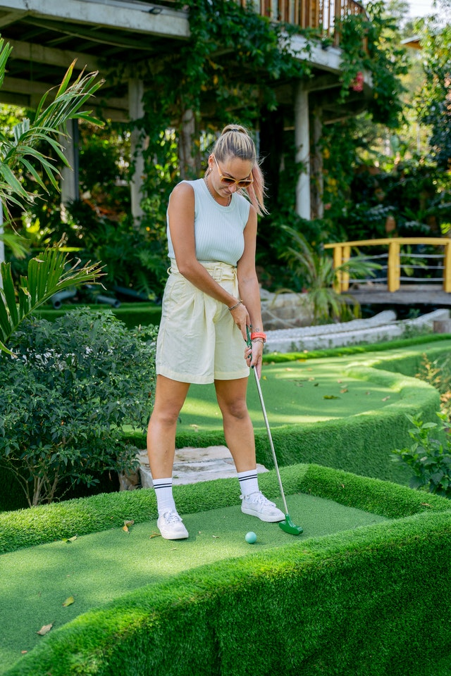 Woman playing golf in fashionable outfit
