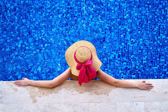 a woman with a stylish hat relaxing in a pool