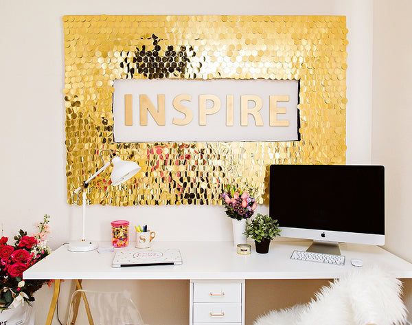Office with gold sequin wall and desk with mac computer