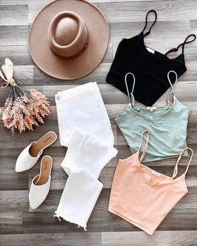 Assortment of crop tops, white jeans, white flats, and beige hat
