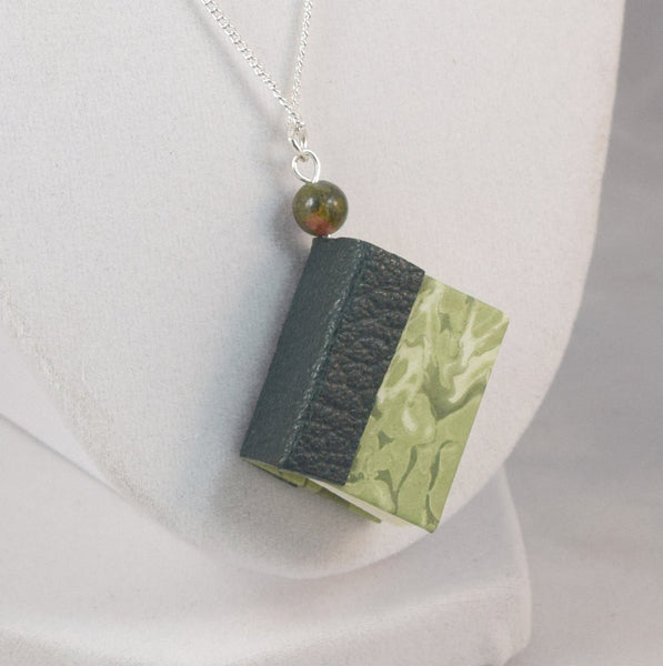 green book pendant displaying leather spine marbled paper cover