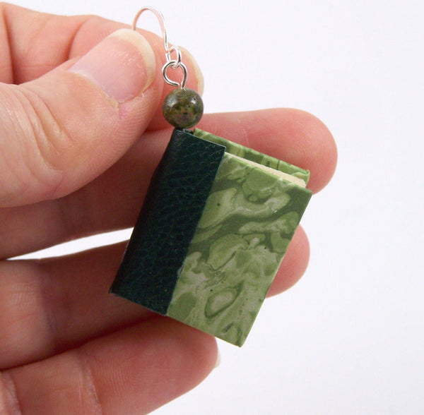 miniature book earring displayed with fingers