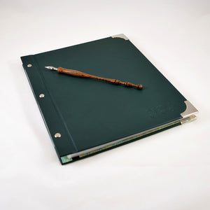 leather portfolio album displayed with turned wood calligraphy pen