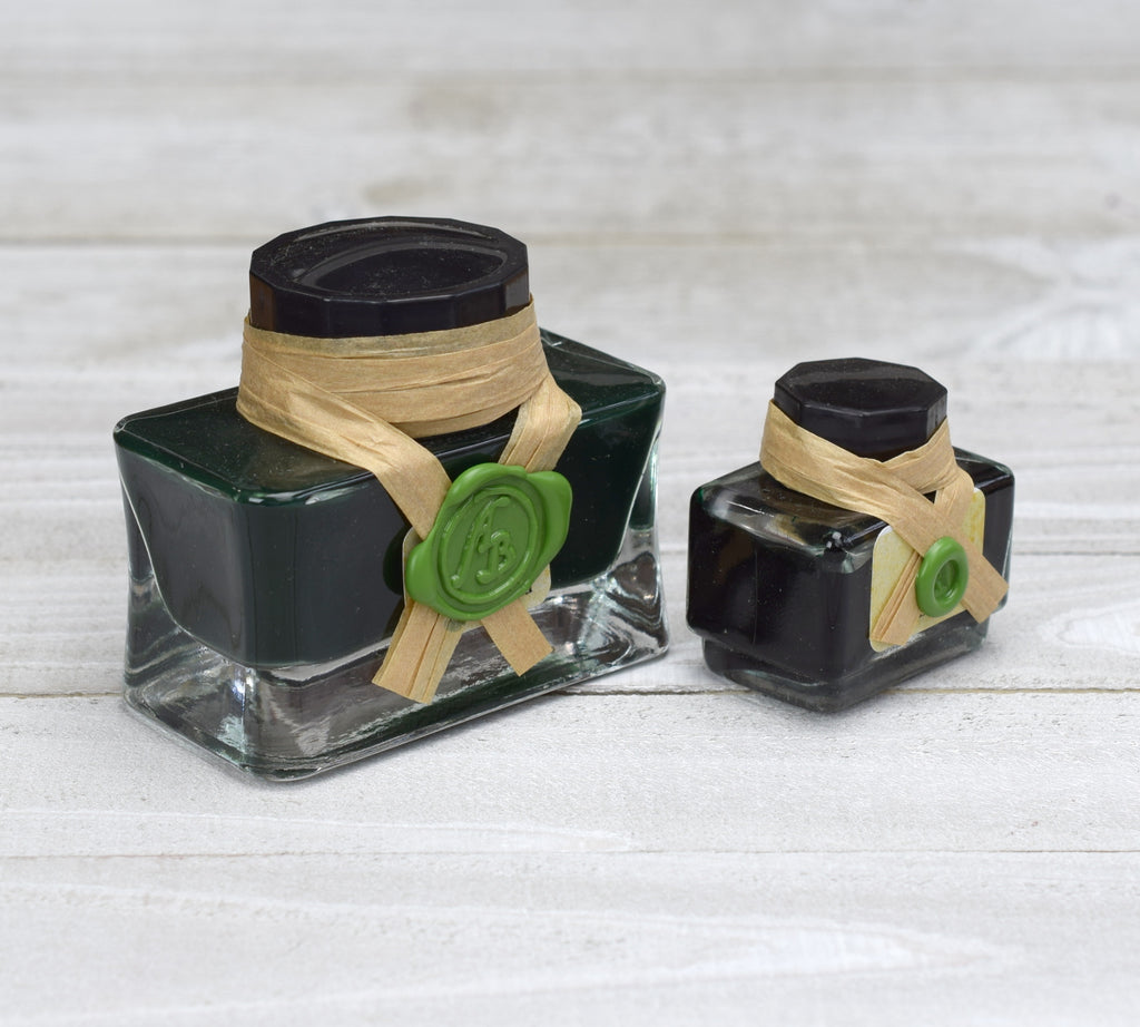 Two glass bottles of green ink