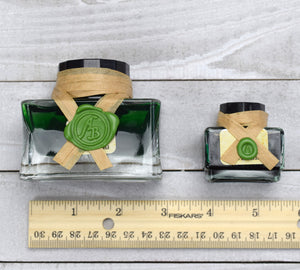 Ink bottles by ruler for scale
