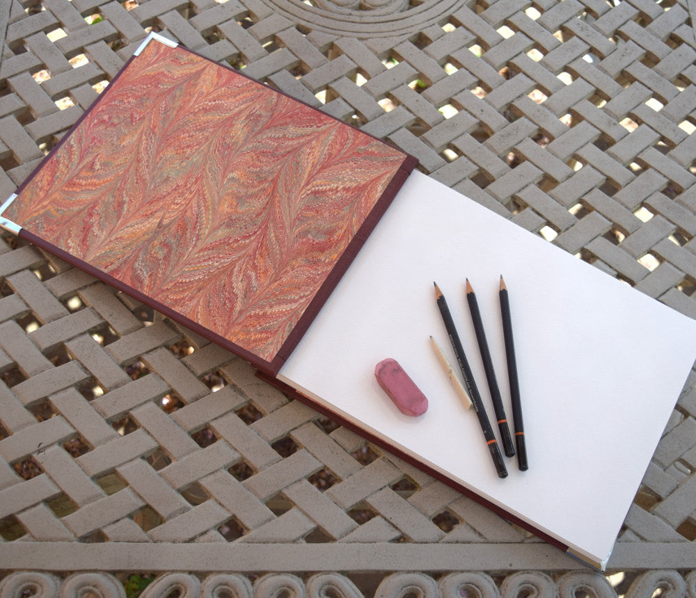 sketchbook open to display facing marbled paper and sketch pages