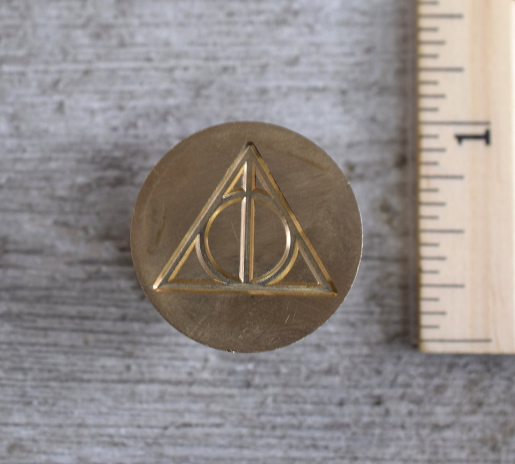 closeup of deathly hallows brass stamp head