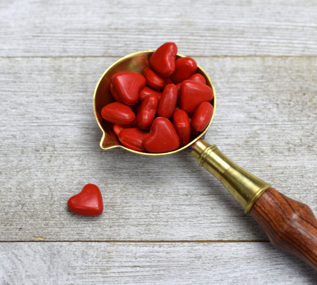 closeup of red wax hearts in brass spoon