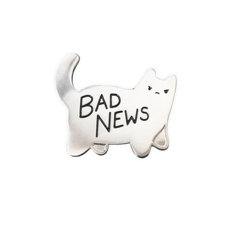 silver enamel pin in shape of angry cat with text bad news