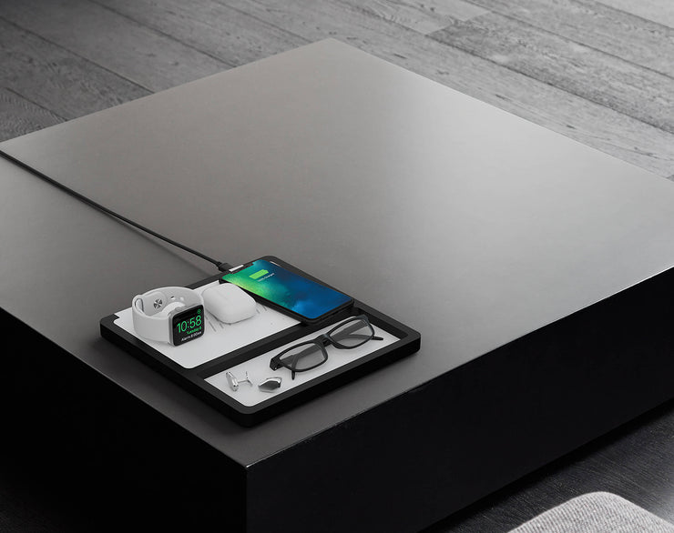 NYTSTND TRIO TRAY  wireless charger and tray-organizer, white leather top, black wooden base, lifestyle picture, charger on the table