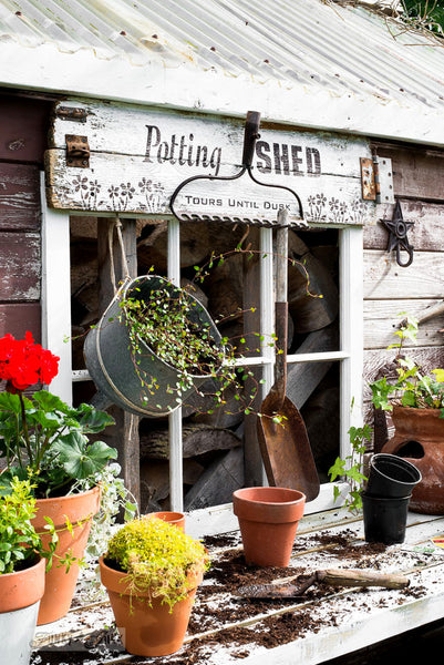 Potting Shed rake sign on a shed with Funky Junk's Old Sign Stencils. Paint professional looking vintage farmhouse styled garden signs onto reclaimed wood with a stencil in minutes!