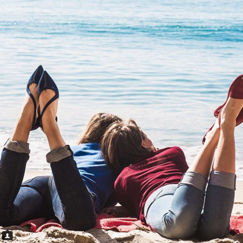 two women on the beach in jeans and jelly shoes