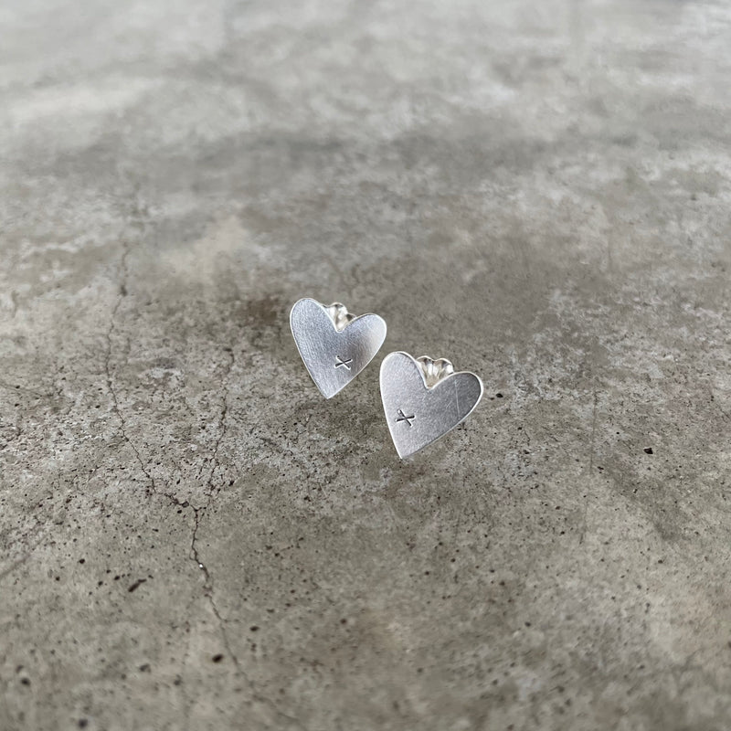 tiny matte sterling silver heart posts with small x detail.