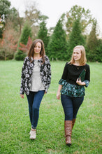 two women walking in grass, one wearing floral fleece jacket over striped top