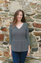 model standing against stone wall wearing black and white striped top and denim