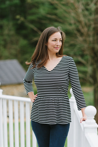 model wearing black and white v neck top with peplum detail