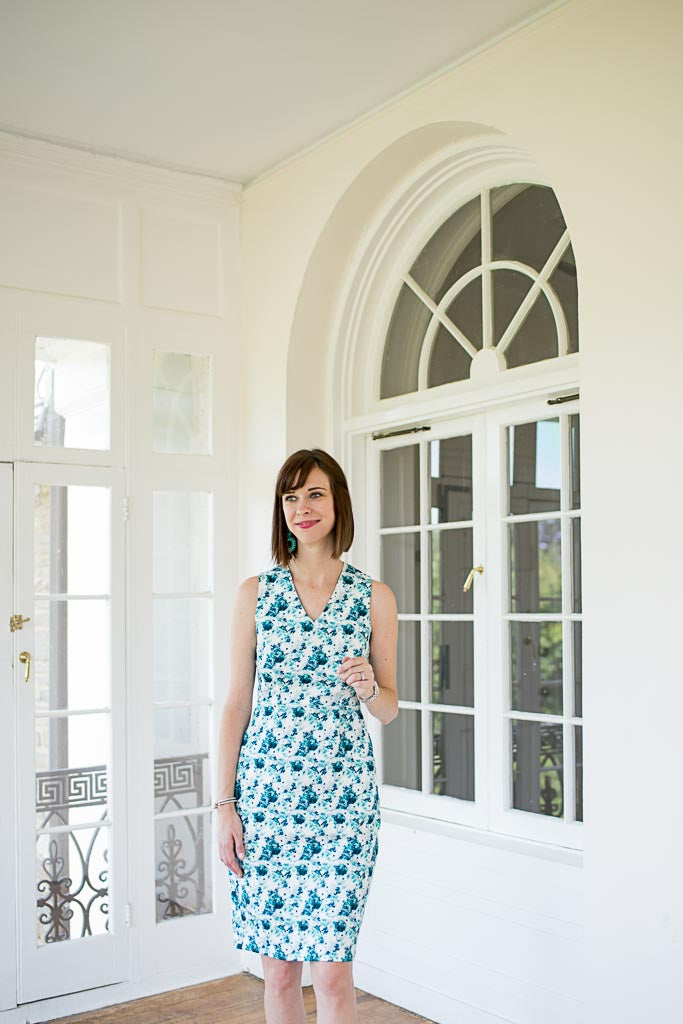 model wearing a sheath dress in blue and white floral