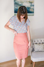 model has hand on waistband of coral denim skirt and is looking down