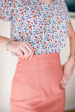 close up of waistband on coral denim skirt, models hand is on waistband.