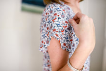 model touching sleeve on floral top