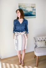 model wearing striped paper bag waist skirt with button down chambray top