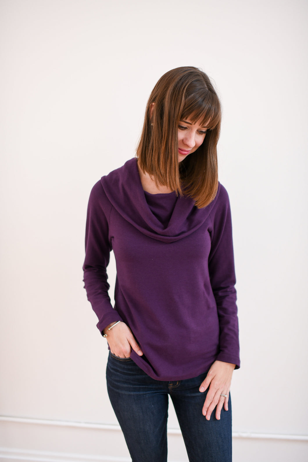 model wearing cowl neck top in plum with dark denim