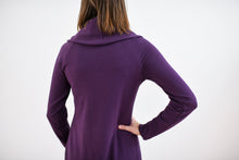 view of back of cowl neck dress in plum. model has hand on hip.